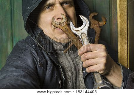 Worker wearing protective coat holding a bunch of hand tools in front of his face. Studio cropped portrait