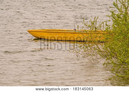 Small wooden yellow boat drifting in lake with choppy water with a lush green bush covering the rear part of the boat