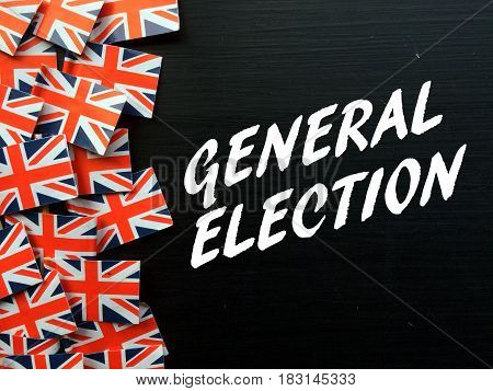 The words General Election in white text on a blackboard with several Union Jack flags of the United Kingdom