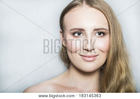 Portrait with face of young blonde beautiful girl with nude make up and long healthy shiny hair, smiling, looking and posing with nude neck and shoulder on white background