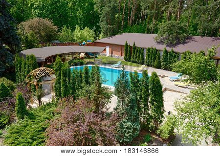 Luxury swimming pool beside the modern hotel and spa resort. Landscape design of resort territory. Beautiful trees and bushes.