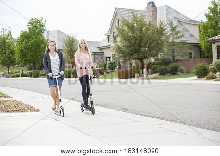 Two smiling attractive women having fun riding scooters together along a sidewalk in a beautiful neighborhood