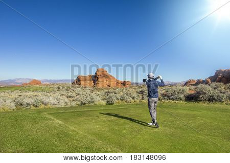 Rear view of a man playing golf on a Sunny day on a beautiful scenic desert golf course in the Southwestern United states.