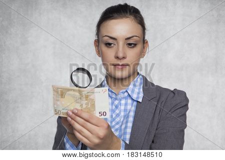 Young Business Woman Checks The Authenticity Of Money