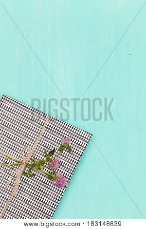 Top view on nice present wrapped in plaid paper and decorated with clover on turquoise background.