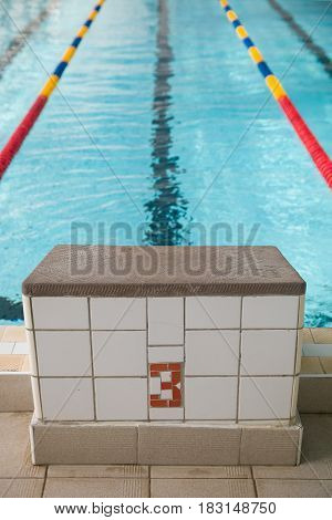 Starting blocks and lanes in a swimming pool. Edge of indoors sport swimming pool. Starting platforms with number 3 for swimming races and competitions. Sport and health concept
