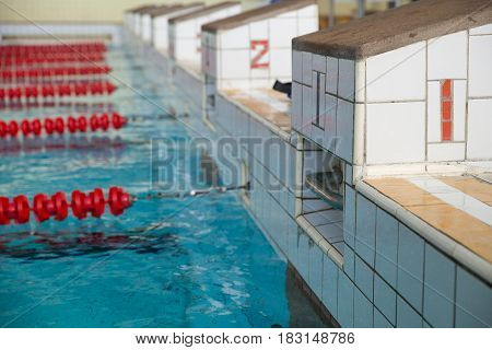 Starting blocks and lanes in a swimming pool. Edge of indoors sport swimming pool. Starting platforms with numbers for swimming races and competitions. Sport and health concept