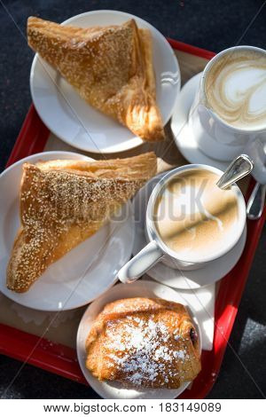 Coffe break at work. Top view on puff pastry and coffee cups on the table outdoors. Croissants and a cups of delicious coffe in a cafe on a sunny day.
