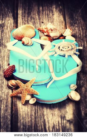Summer holiday setting with flip flops and sea shells on old wood background