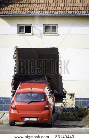 Red car parked on room behind hole in wall.