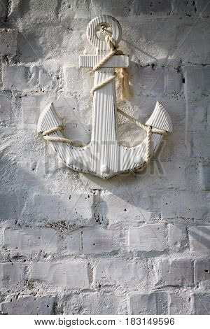 Wooden anchor on white brick wall background.