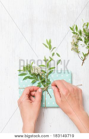 Top view on woman's hands decorating birthday gift with garden tree branch with flowers. Packing present for the party. Wrapping gift with flower decor and turquoise paper. Holidays concept.