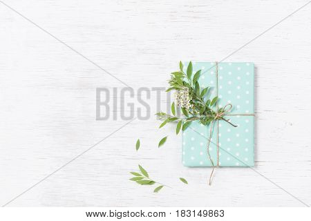 Top view on decorated birthday gift with garden tree branch and flowers. Packing present for the party. Wrapping gift with flower decor and turquoise paper. Holidays concept. Flat lay.