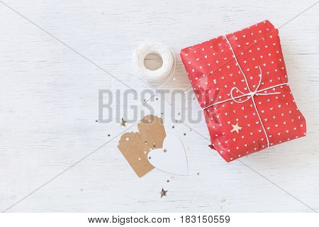 Top view on nice celebration gift with ribbon and tags. Wrapped present for Christmas birthday or any party on white wooden background.