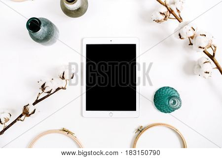 Blogger or freelancer workspace with blank screen tablet and cotton at white background. Flat lay top view minimalistic decorated home office desk.