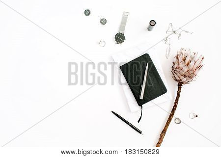 Blogger or freelancer workspace with protea flower notebook and feminine accessories on white background. Flat lay top view minimalistic decorated home office desk. Beauty blog concept.