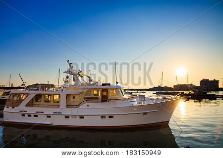 White yacht in commercial port, motor boats in Black sea at sunset.