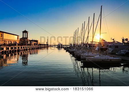 Commercial port of yachts, motor and sailing boats in Black sea at sunset.