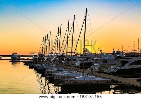 SOCHI, RUSSIA - MARCH 09, 2017: Sailing boats and luxury yachts docked in sea port in Black sea at sunset.