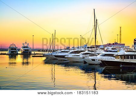 Luxury yachts docked in sea port at colorful sunset. Marine parking of modern motor boats.