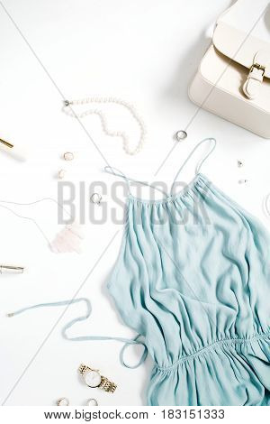 Beauty blog concept. Woman clothes and accessories: blue dress purse watches bracelet necklace rings lipstick on white background. Flat lay top view trendy fashion feminine background.