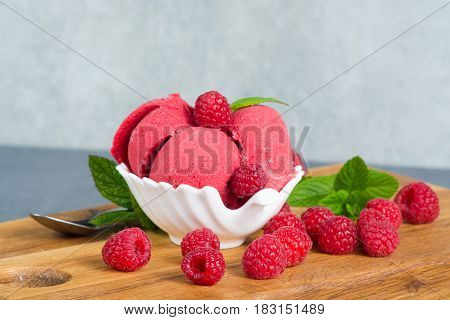 Raspberry ice cream sorbet in white bowl with spoon raspberry mint leaves copy space