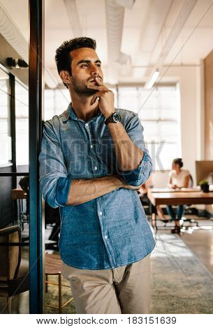 Portrait of young man standing at door looking away and thinking. Thoughtful young male at startup office with colleagues working in background.