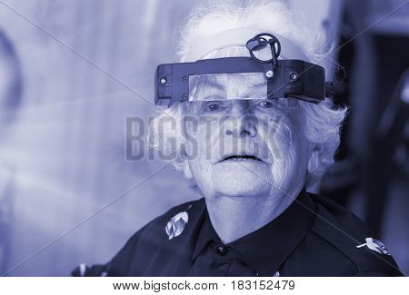 Grandmother in the big special glasses of the electronics engineer, watchmaker, blue tone