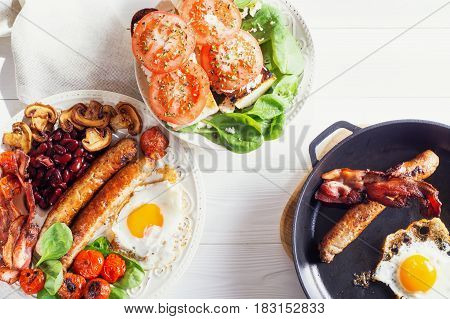 Delicious full English breakfast with fried egg bacon sausage tomatoes beans and mushrooms. Traditional english breakfast on white wooden background top view flat lay.