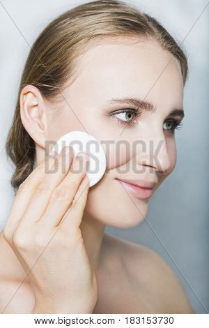 Portrait with face of young blonde beautiful girl with nude make up and with cotton pad in her hand, smiling, looking aside and posing on white background