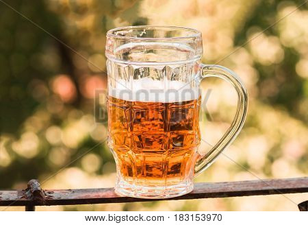 light beer closeup in large glass alcohol on a nature background