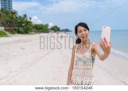 Young Woman taking selfie by cellphone from the beach