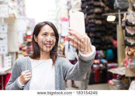 Woman taking selfie by cellphone in street market of Hong Kong