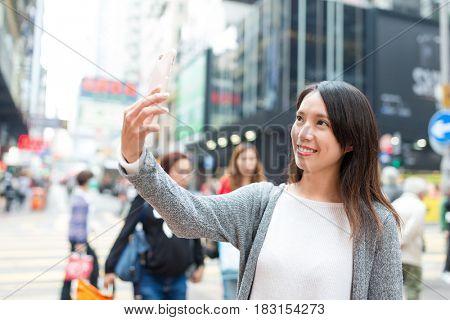 Woman taking selfie by cellphone in Mongkok at Hong Kong