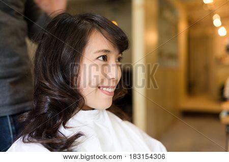 Young Woman having hair cut in salon