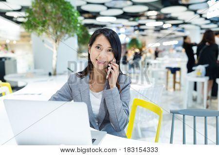 Businesswoman talk to cellphone and working on laptop computer