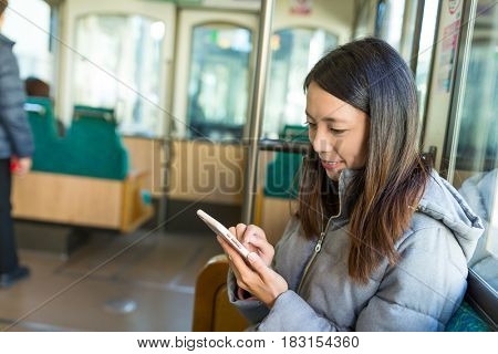 Woman using cellphone in japanese train