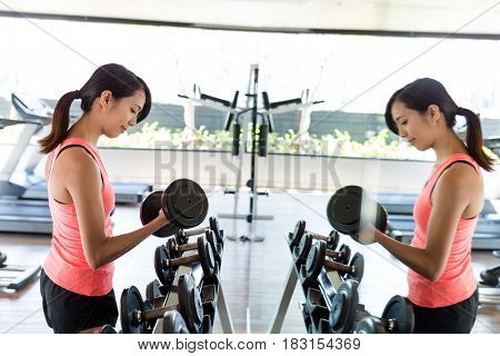 Sport Woman practices weight lifting of the dumbbell in gym