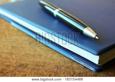 blue notebook and ball pen on an old wooden background close up view with copy space.