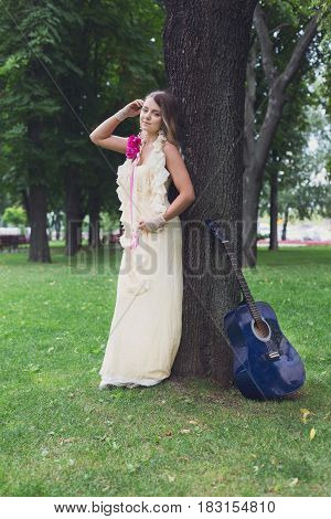 Fashion portrait of beautiful boho style girl in long dress with blue acoustic guitar in sun warm light. Female musician. Woman and musical instrument