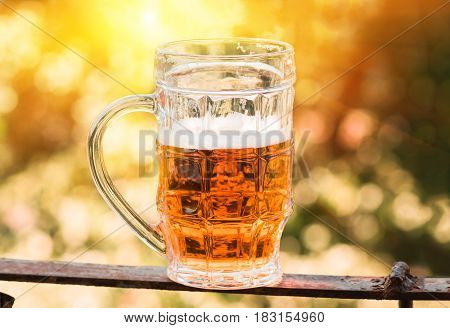 light beer closeup in large glass, alcohol on a nature background