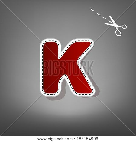 Letter K sign design template element. Vector. Red icon with for applique from paper with shadow on gray background with scissors.