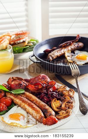 Delicious full English breakfast with fried egg bacon sausage tomatoes beans and mushrooms. Traditional English breakfast.