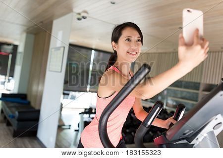 Sport Woman practice on Elliptical machine and taking selfie