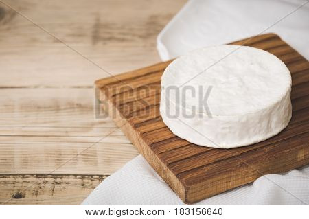 Camembert cheese on wooden board. Serving French homemade soft cheese. Food concept