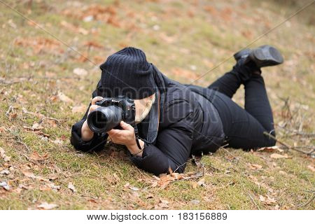 GOMEL BELARUS - 12 April 2017: A woman photographer takes pictures lying on the ground.