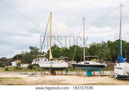The yachts are aground in shallow sea water. Boat run aground in waterless pier or harbor