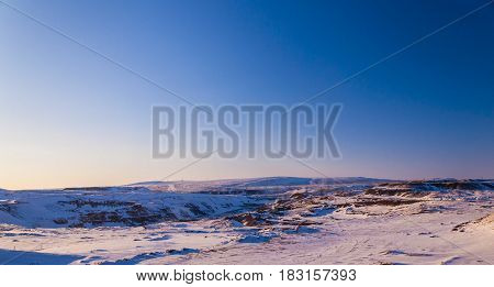 winter landscape against the background of the sky on a sunset and long dark shadows