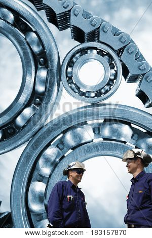 two industry workers with giant ball-bearings machinery in background, slight blue toning