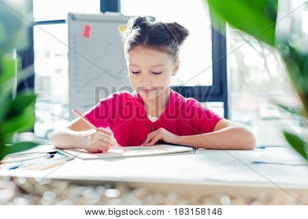 Smiling Little Girl Sitting At Desk And Drawing In Office